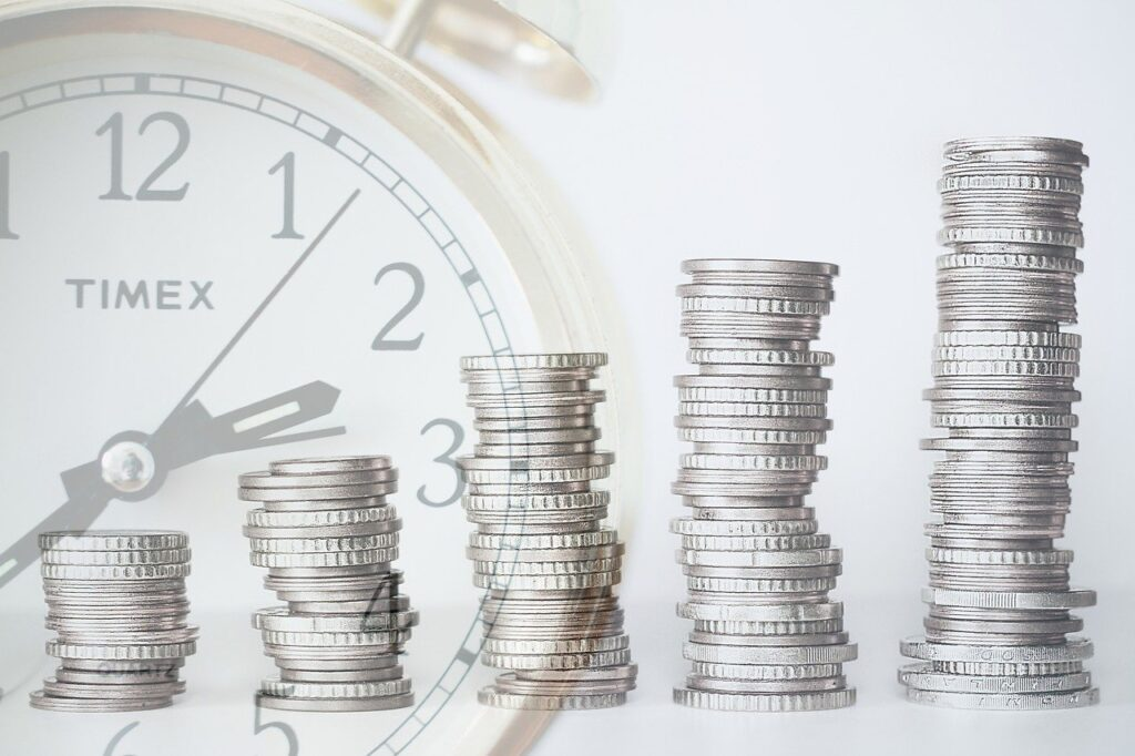 alarm clock and rows of coins for finance and business concept.