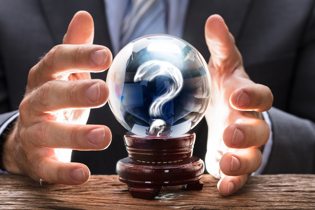 businessman covering crystal ball with smoke forming question mark at wooden table